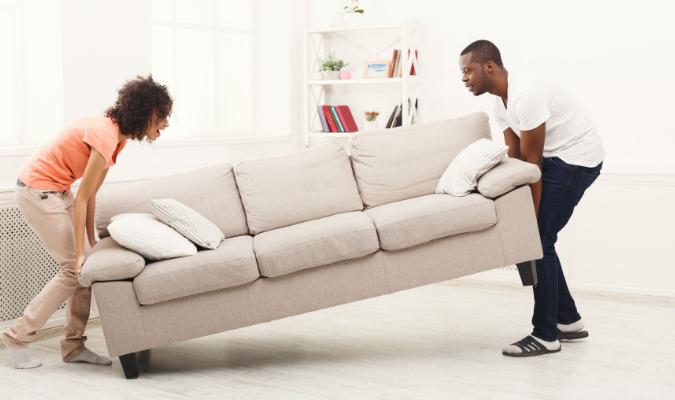 Couple moving heavy furniture - cream sofa