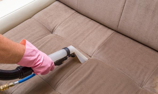 Vacuuming brown microfiber sofa