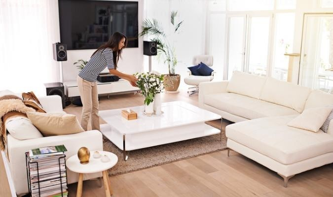 Woman watering plants in a cosy winter living room