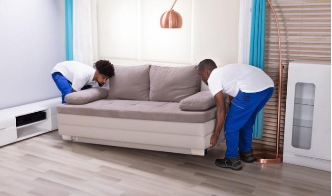 Two men delivering a British-made sofa