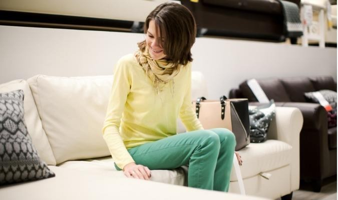 Woman testing the quality of a sofa in a furniture shop