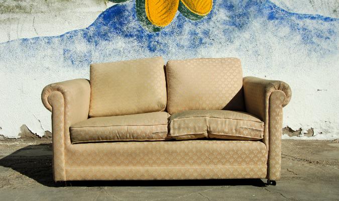 Yellow fabric sofa with flat lumpy cushions
