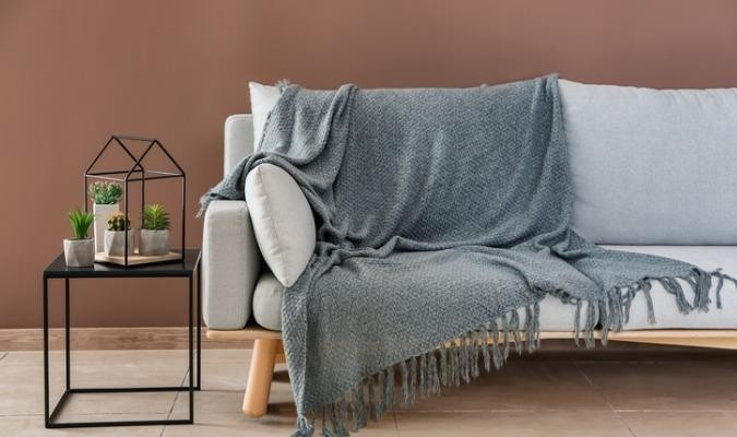 Grey sofa with a blanket in a brown modern living room