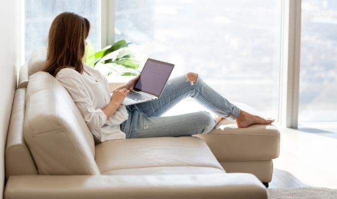 Relaxed -woman -using -laptop -sitting -on -sofa -at -luxury -home -picture -id 994243558