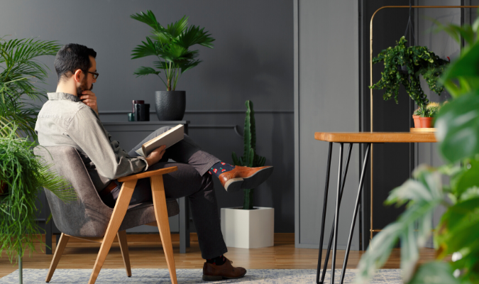 Man Reading In Room With Plants