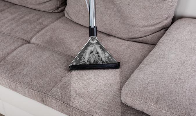 A grey sofa being deep cleaned